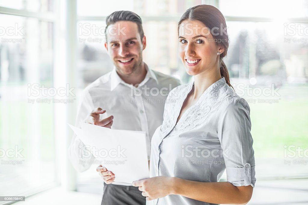 Portrait of happy young businesspeople discussing over documents in office – Foto