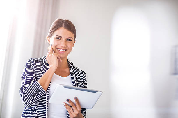 Portrait of happy young businesswoman using digital tablet in office – Foto