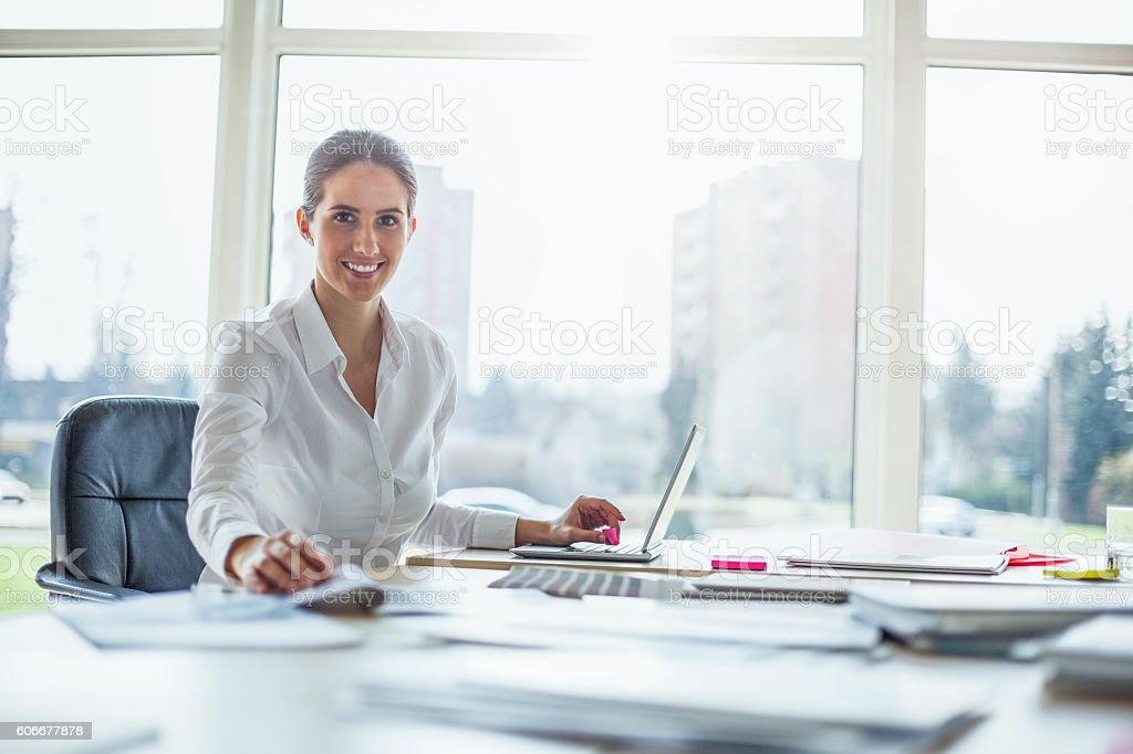 Portrait of happy young businesswoman using laptop at office desk stock photo