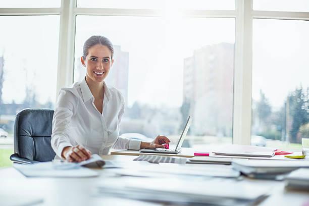 Porträt von glücklicher junger Geschäftsfrau benutzt Laptop am Schreibtisch – Foto
