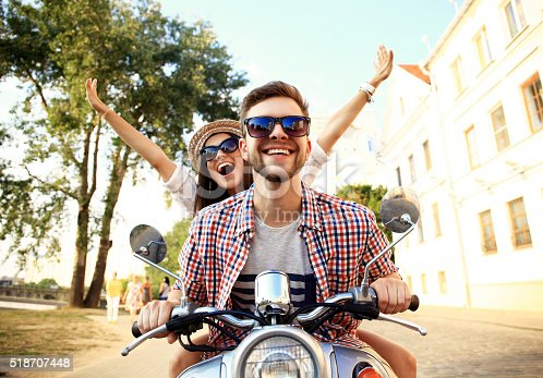 istock Portrait of happy young couple on scooter enjoying road trip 518707448
