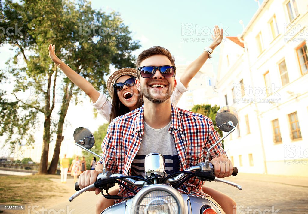 Portrait of happy young couple on scooter enjoying road trip bildbanksfoto
