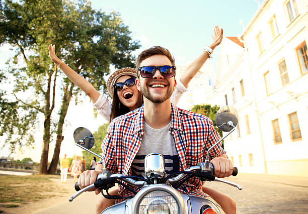 Portrait of happy young couple on scooter enjoying road trip stock photo