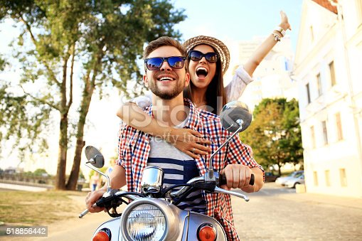 istock Portrait of happy young couple on scooter enjoying road trip 518856442