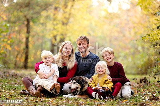 A portrait of a happy young family with three cute, smiling, children and their pet dog sitting outside in the woods on an Autumn day.