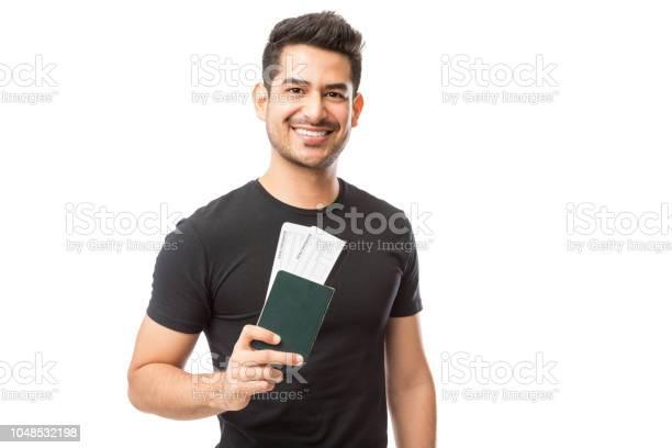 Portrait of happy young guy holding passport and boarding pass picture id1048532198?b=1&k=6&m=1048532198&s=612x612&h=bsb0em1gjfke zju4in2l41n sgmoaopddvwy4nethk=