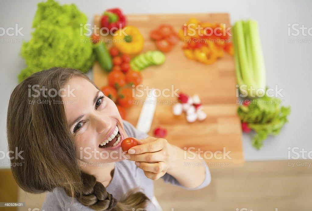 Porträt der glückliche junge Hausfrau mit Gemüse in der Küche – Foto