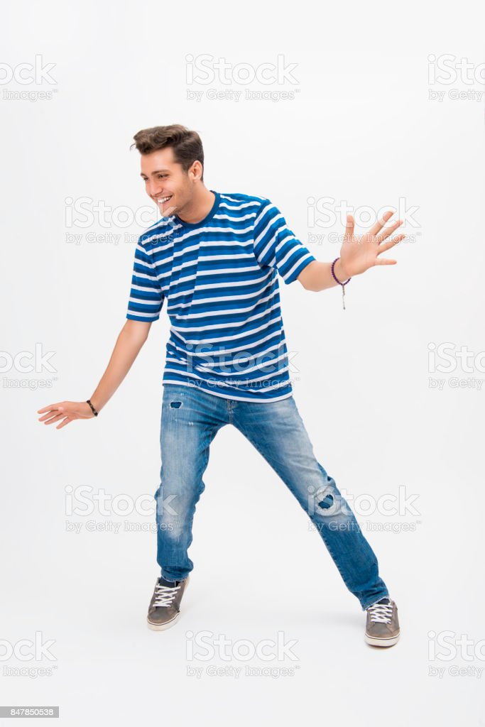 Portrait of happy young man dancing over white background stock photo