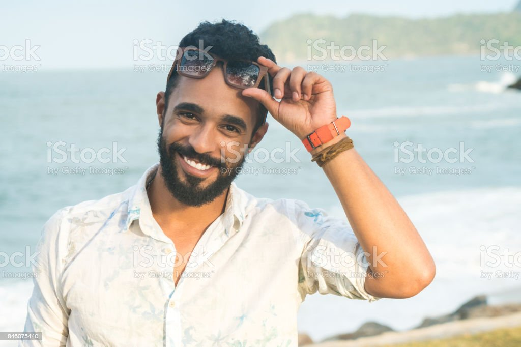 9685fc20b1c5 Portrait of happy young man holding sunglasses at beach - Stock image .