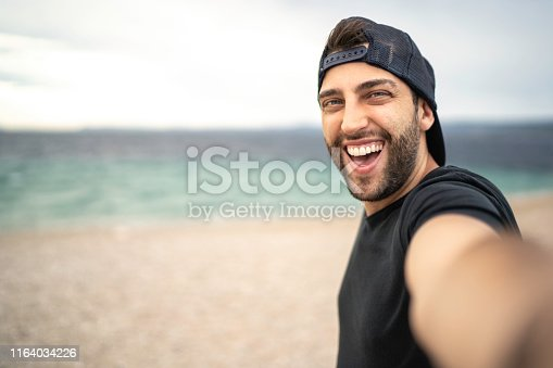 Portrait of happy young man taking a selfie at the beach