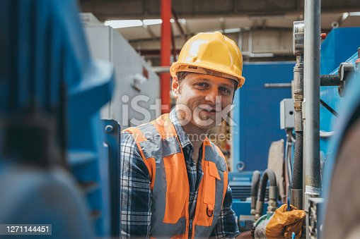 Portrait of a happy technician or engineer man looking at camera and smiling while checking, opening or adjusting valve equipment in industrial site factory or utility.