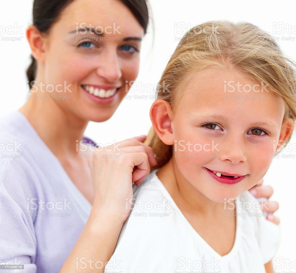 Portrait of happy young mother combing hair of daughter royalty-free stock photo
