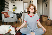 istock Portrait of happy young redhead woman sitting in a lotus position 1224568244