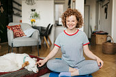 istock Portrait of happy young redhead woman sitting in a lotus position 1224568279