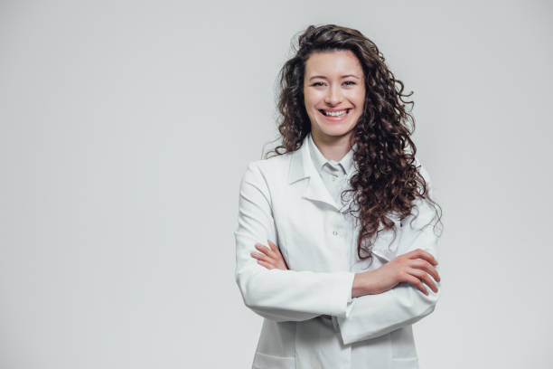 portrait of happy young smiling girl doctor. dressed in a white robe. evenly standing with crossed hands on a gray background. - лабораторный халат стоковые фото и изображения