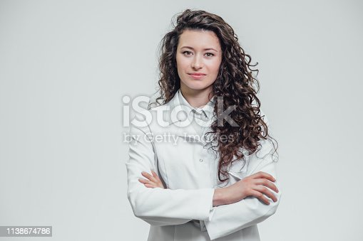 Portrait of happy young smiling girl doctor. Dressed in a white robe. Evenly standing with crossed hands on a gray background. Has long black beautiful hair.