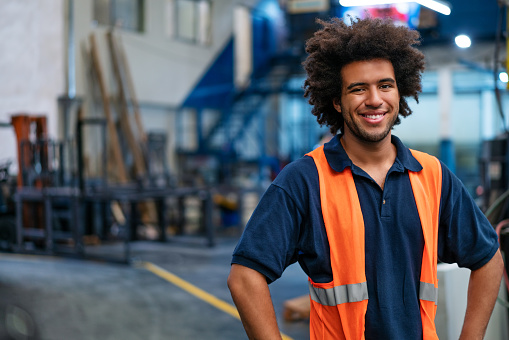 Portrait of a happy young man working in warehouse. Male warehouse worker in uniform looking at camera and smiling.