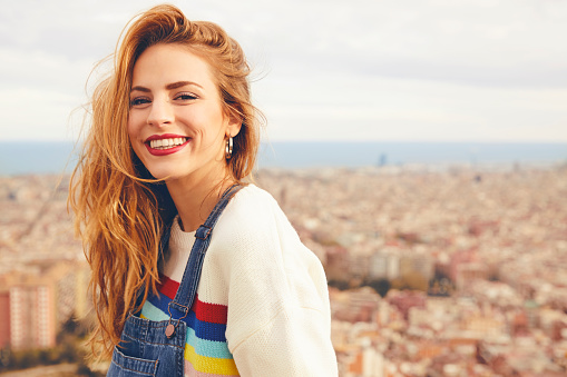 istock Portrait of happy young woman against cityscape 695593548
