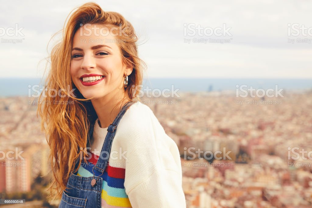 Portrait of happy young woman against cityscape stock photo