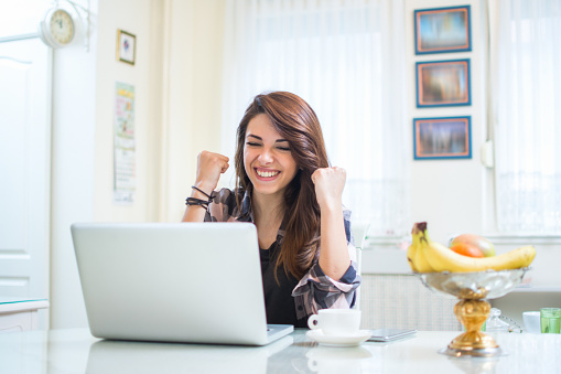 Portrait of happy young woman celebrating success with arms up in front of laptop at home.