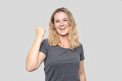 500150419 istock photo Portrait of happy young woman cheering by shaking fist over gray background 1180555201