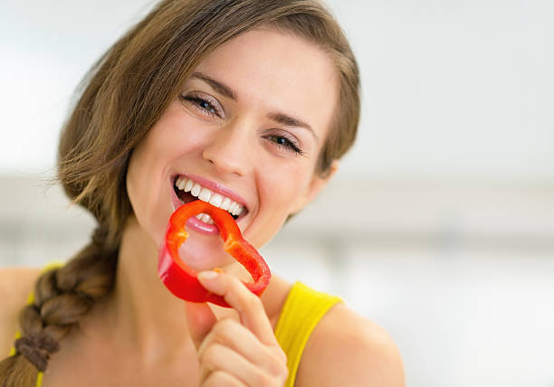 Porträt der glückliche junge Frau isst Paprika in der Küche – Foto