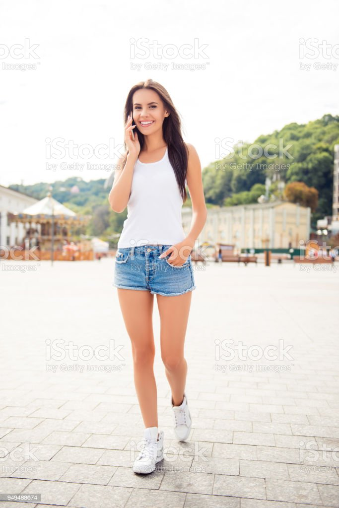 Portrait of happy young woman having walk and talking on phone