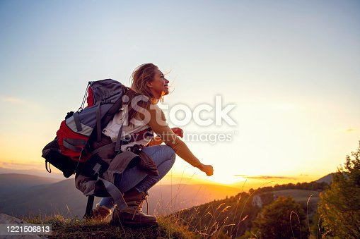Portrait of happy young woman hiking in the mountains.