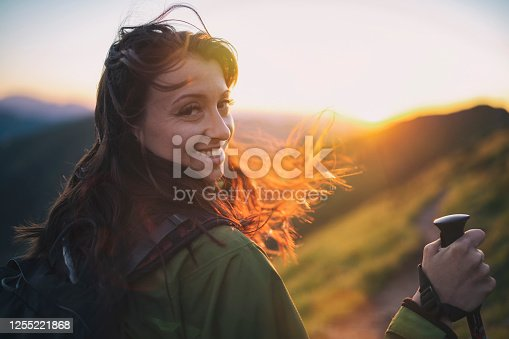 Portrait of beautiful happy young woman hiking in the mountains, she looking at camera and smiling, sunset.