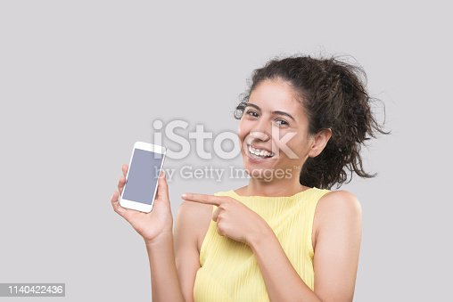 1132512623istockphoto Portrait of happy young woman pointing at copy space in smart phone against gray background 1140422436