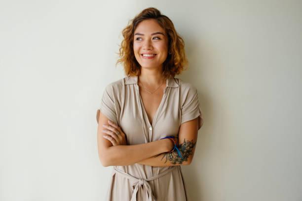 porträt der glückliche junge frau posiert im studio - tattoos frauen arm stock-fotos und bilder