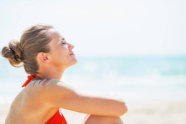 ritratto di felice giovane donna rilassante sulla spiaggia - abbronzarsi foto e immagini stock
