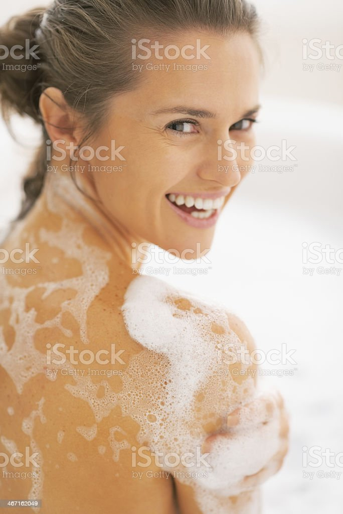 portrait of happy young woman washing in bathtub stock photo
