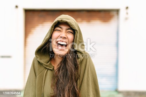 A portrait of a happy young woman wearing a hoodie .