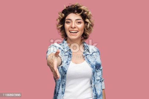 Portrait of happy young woman with curly hairstyle in casual blue shirt standing, toothy smile, looking and giving her hand to greeting and handshake. indoor studio shot, isolated on pink background.