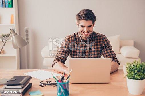 istock Portrait of happy young writer typing new book on laptop 945550248