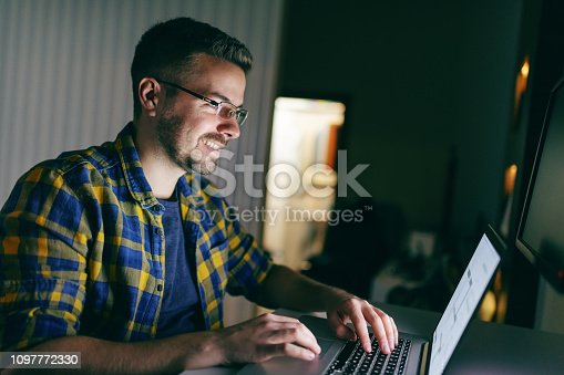 istock Portrait of hard working smiling employee using laptop for work while sitting in the office late at night. 1097772330