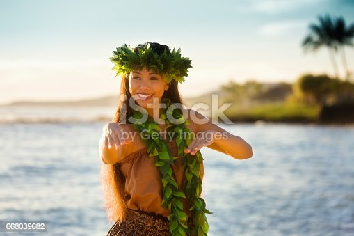 A beautiful Hawaiian Hula dancer dancing on the beach of the tropical Hawaiian islands. She is wearing a traditional Hula dance dress with a lei and a head dress. Photographed in vertical format with copy space in Kauai, Hawaii.