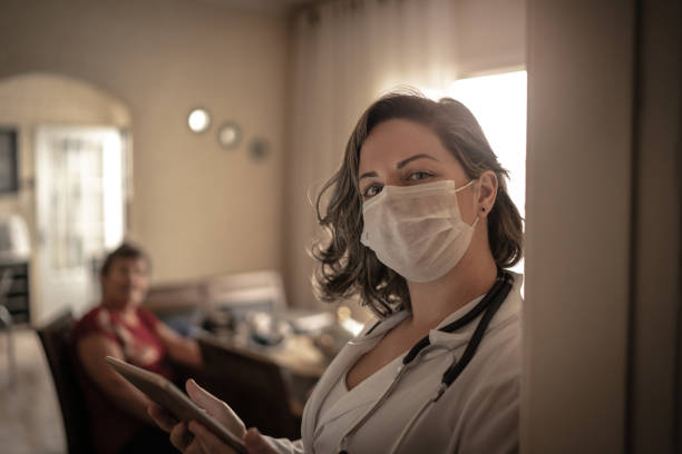 portrait of health visitor and a senior woman during home visit - charity and relief work stock pictures, royalty-free photos & images