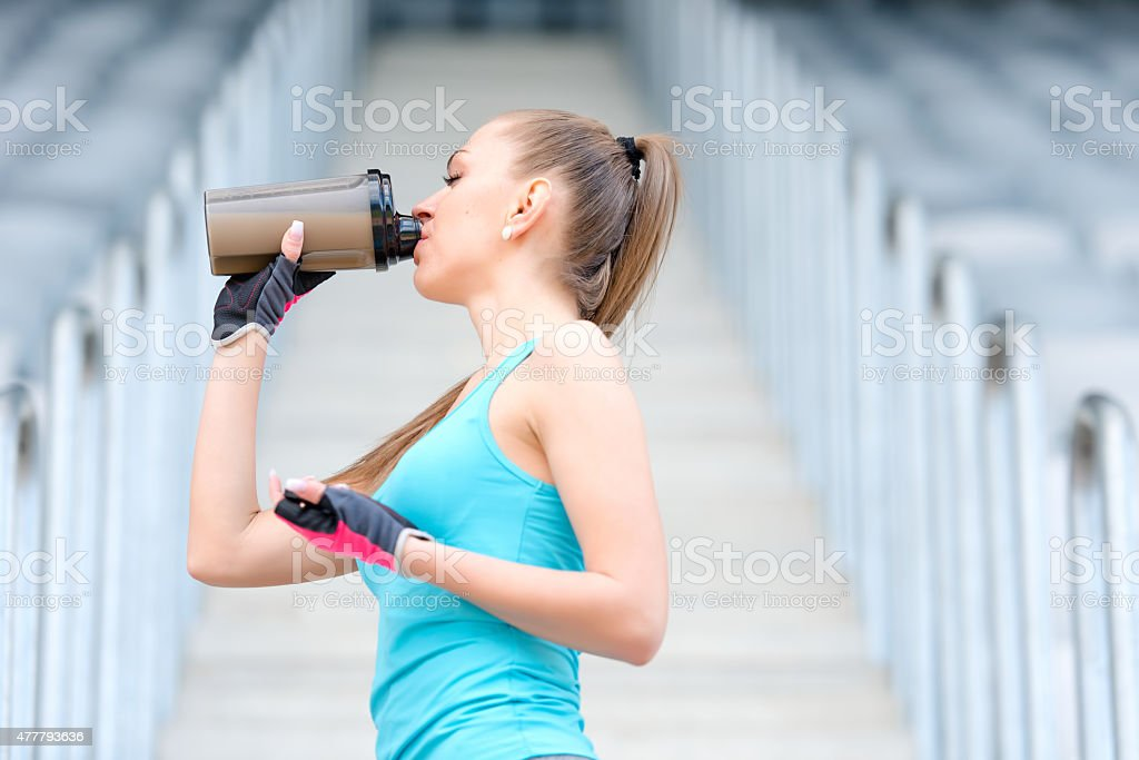 Portrait of healthy fitness girl drinking protein shake stock photo