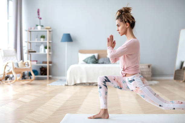 Portrait of healthy lady going yoga workout in room. stock photo