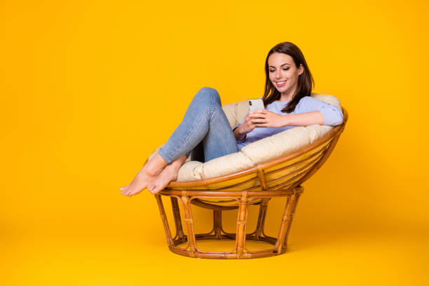 Portrait of her she attractive pretty lovely cheerful cheery girl sitting in comfy wicker chair using device browse media isolated bright vivid shine vibrant yellow color background stock photo