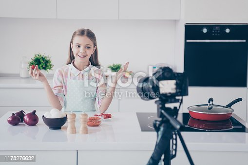 488109116istockphoto Portrait of her she nice attractive beautiful charming lovely cute cheerful cheery pre-teen girl making useful vitamin salad recording video lesson in light white interior kitchen house indoors 1178276632