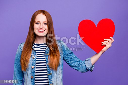 Portrait of her she nice attractive charming cute lovable lovely cheerful straight-haired lady holding in hands showing big large bright vivid heart isolated over bright vivid shine violet background.