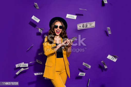 Portrait of her she nice attractive cheerful cheery positive trendy luxury, wavy-haired lady throwing 100 hundred million expenses isolated over bright vivid shine violet lilac background