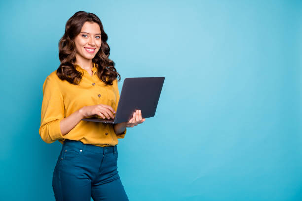 Portrait of her she nice attractive confident cheerful cheery wavy-haired girl holding in hands laptop creating web design isolated on bright vivid shine vibrant green blue turquoise color background stock photo