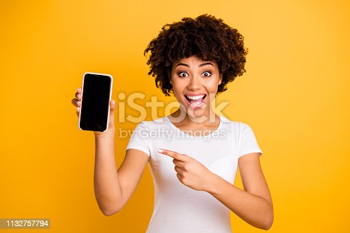Portrait of her she nice attractive lovely charming cheerful cheery ecstatic wavy-haired lady holding in hands cell showing black screen isolated on bright vivid shine yellow background.