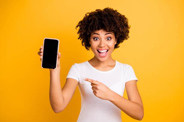 明るい鮮やかな輝きの黄色の背景に隔離された黒い画面を示す手のセルに保持している彼女の素敵で魅力的で美しいチャーミング陽気陽気な恍惚とした波状の髪の女性の肖像画 - 見せる ストックフォトと画像