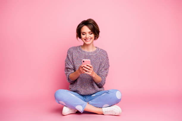 Portrait of her she nice attractive lovely charming pretty cute cheerful cheery brown-haired girl sitting using cell 5g app isolated over pink pastel color background stock photo
