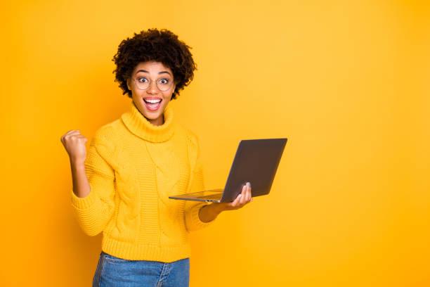 portret van haar ze leuk aantrekkelijk mooi charmant slim slimme vrolijke golvende-haired meisje vasthouden in handen laptop vieren winnen geïsoleerd over heldere levendige glans levendige gele kleur achtergrond - opwinding stockfoto's en -beelden